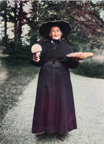An old woman holds up two giant mushrooms